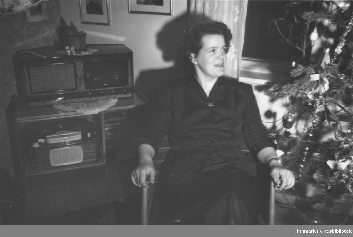 Jul, ca. 1960-1961. Ragnhild Ebeltoft sitter ved juletreet, i bakgrunnen et radiokabinett med platespiller
