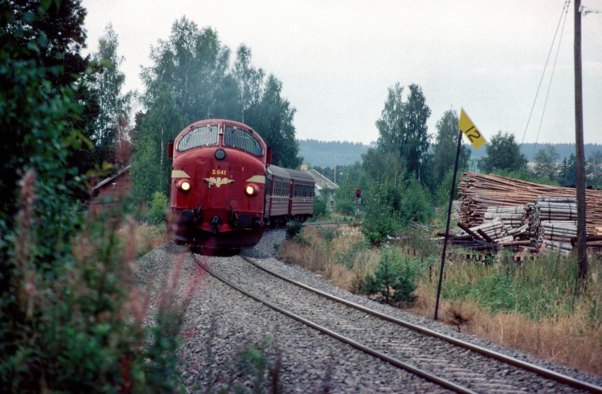 NSBs dagtog, tog 301 Oslo - Trondheim over Røros, kjører ut fra Ilseng stasjon med dieselelektrisk lokomotiv Di3b 641. I bakgrunnen sees enkelt innkjørsignalapparat B på Ilseng stasjon.