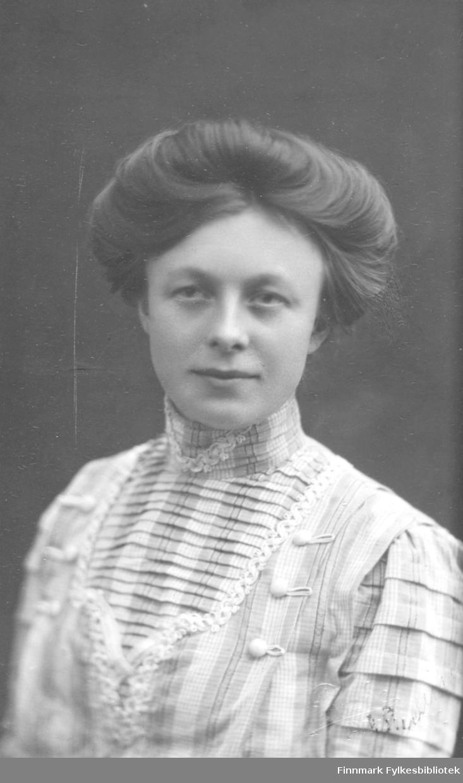 """Portrett av Sigrid Dahl. Hun er kledd i en lys rutete kjole. Håndskrift, tekst bak bildet: """"Til herr lærer Korby. 15.10.1910.""""  Trolig er det snakk om lærer Werner Alfred Korbi."""