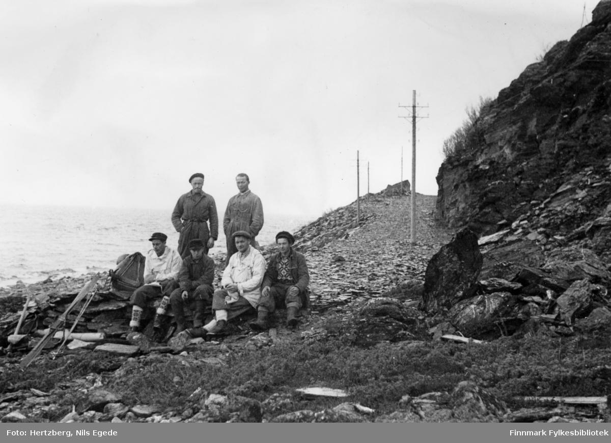Våren 1948 ble det foretatt en befaring Vadsø - Smalfjord - Sjursjok - Ifjord - Bekkarfjord - Hopåseidet - Mehamn - Kjøllefjord - Vadsø. Med på turen var: Avd.ing. Nils E. Hertzberg, oppsynsmann Johannes Foslund, og tekniker Godtfred Karlsen. Se også bildene 313-324. Arbidslaget drev på med avsluttende vinterarbeide. Fjellakkord. Sittende fra venstre: Godtfred Karlsen, Ivar Persen, Johannes Foslund og Ole Einarsen. Stående bak: Nils Nyborg og Johan R. Johnsen.