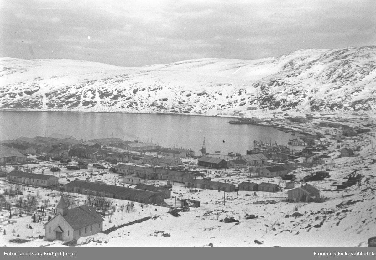Bydelen Haugen i Hammerfest, høsten/vinteren 1945.  Gravlunden med gravkapellet står nede til venstre på bildet. Noen flere brakker er satt opp på området som er delvis snødekt, men en del ruiner ses også. Brakka nede til venstre på bildet er Selmer Eriksens fiskebutikk og en avlange brakka rett ovenfor er brakke nr. 45. Dette var kommuneadministrasjon og noen boliger. Kaier er under bygging i havna og hospitalskipet Elieser IV ses i indre havn. En del brakker er satt opp videre nedover byen mot bydelen Molla. Fjellet til høyre på bildet er Mollafjell som går videre bortover mot Fuglenesfjell.