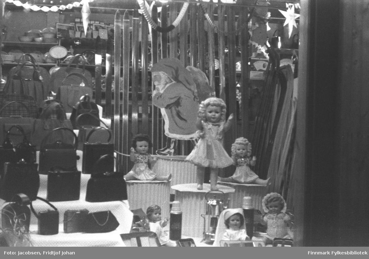 Juleutstilling i butikken til Trygve Nissen etter andre verdenskrig. Små søyler med dukker og nisser står til høyre på bildet mens håndvesker står til venstre. Bak denne utstillingen står en del langrenns-ski. Et par stjerner ses øverst på bildet og en del andre saker står på hyllene i bakgrunnen.
