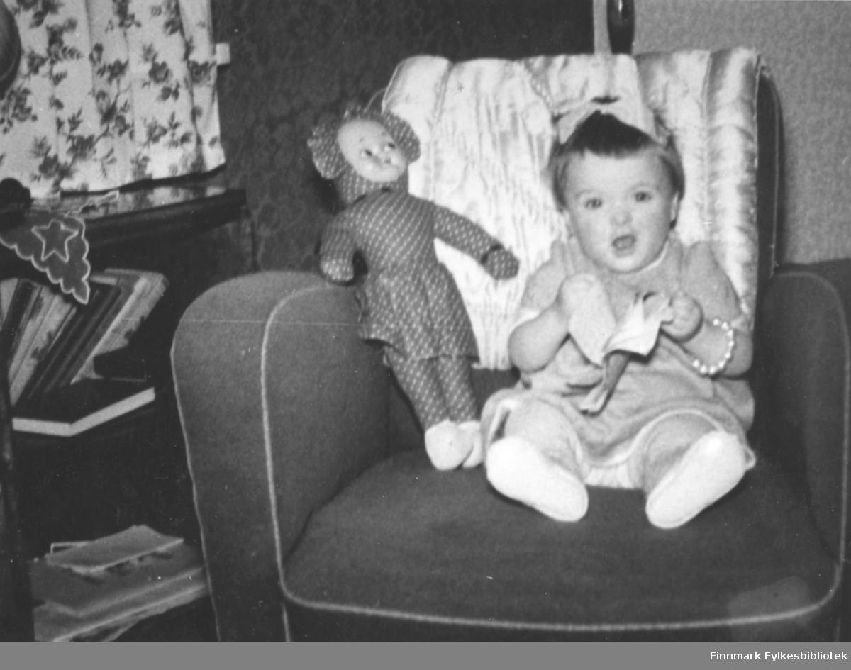 Svanhild Rushfeldt sitter i en lenestol og leser for tøydukken sin 1956/57. Rundt armen har hun et perlearmbånd og på hodet en stor sløyfe. Dukken ligger vedsiden av henne og på ryggen av stolen er det plassert et teppe. I øverste venstre hjørne kan man se deler av en gardin med blomster på og på hyllen under ser man deler av en duk med stjerne motiv. I hyllen er det stablet bøker.