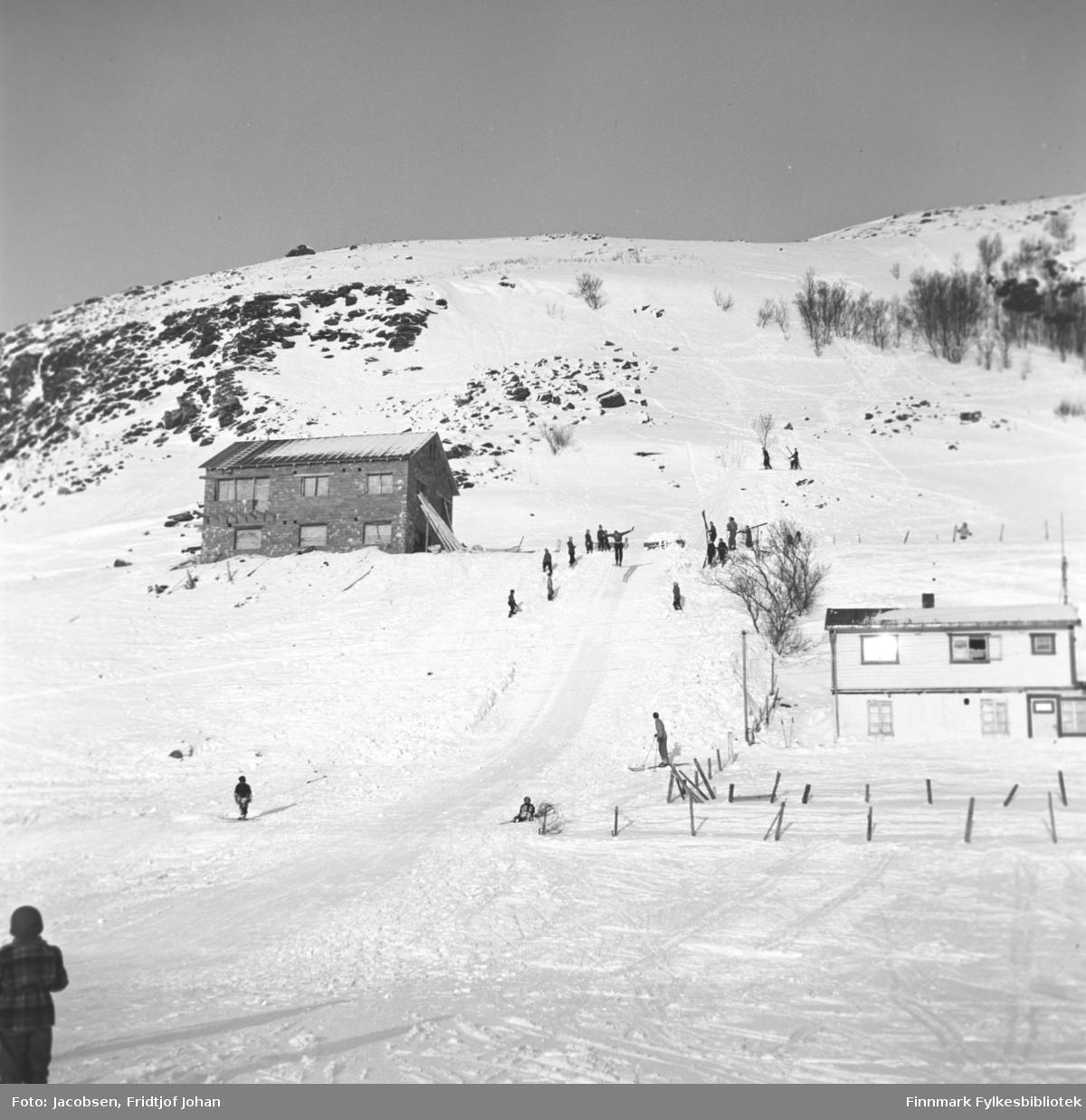Skihopping i Kallanbakken. En del mennesker er i bakken og en står helt nede til venstre på bildet på det is- og snødekte Storvannet. Noen trær står oppe i fjellsiden på Breiliafjell. Huset til høyre tilhørte Maia Wilhelmsen og gjerdet rundt huset stikker såvidt opp av snøen. Huset til venstre er Sneves.