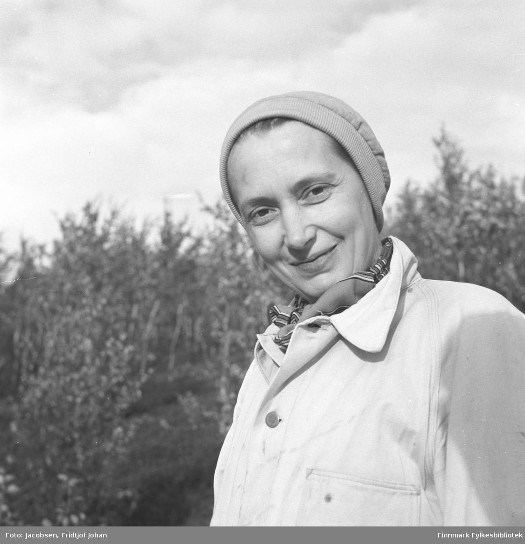 Aase Jacobsen på tur. Hun har en hvit/lys jakke på seg med et mønstret skjerf/tørkle rundt halsen. Hun har en lue på seg og i bakgrunnen ses endel løvtrær.
