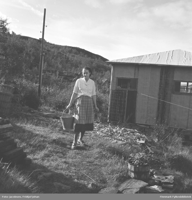 Aase Jacobsen på eiendommen til sin far, Arne Nakken, i Rypefjord. Hun har en lys, kortermet bluse på seg og rutet skjørt med forkle utenpå. Hun bærer på en metallbøtte i sin høyre hånd. Brakka til høyre fikk Aase og Fridtjof bruke som hytte etter at Arne og Sigrid Nakken flyttet inn i bolighuset da det var ferdig. En trestamp brukt som blomsterkrukke ses nede til høyre på bildet. En trapp går opp til Nakkens hus til venstre på bildet. Litt lengre bort står en el-stolpe. Flere løvtrær står i dalsiden bakerst på bildet.