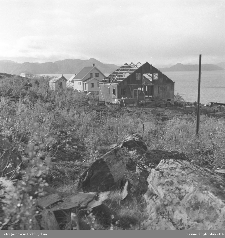 Dette bildet er tatt om sommeren og viser naboeiendommene til Arne Nakken i Rypefjord. Huset som er under bygging tilhørte Bjarne og Ranveig Berg. huset bak det tilhørte lærerinne Anna Andersen. Et lite bygg/uthus står ved siden av det og taket på et par hus ses bak de to bygningene. Et gjerde er satt opp rundt huset og en snøskjerm ses lengst borte på bildet. Ganske store steiner ligger på bakken nærmest kamera og til høyre står en el-stolpe. Mye gress og noen busker står på store deler av området. Fjellet i bakgrunnen er Seiland.