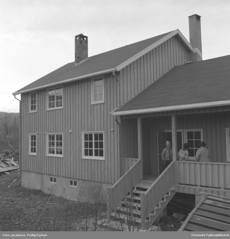 Fotografi av Telegrafverkets hytte i Bjørnlia, Repparfjorddalen. Mannen på trammen med ansiktet mot kameraet er Alf Henriksen. Han er iført en strikkejakke og mørke bukser. To damer i mønstrete gensre står ved siden av. Hytta er ganske stor med stående panel og pappdekke på taket. Flere sprossevinduer med hvite karmer ses på langveggen og tilbygget. To skorsteiner ses på taket og en stabel med material ligger på bakken helt til venstre på bildet. Noen bjørketrær står helt foran på bildet og på siden av huset.