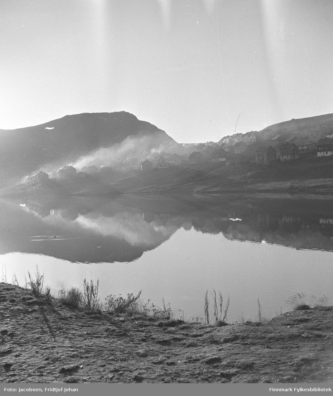 Morgenstemning ved Storvannet i Hammerfest. Bredden i nedre del av vannet ses foran på bildet. Bebyggelsen på andre siden av det blikkstille vannet er Idrettsveien, Rairo og Skiveien i bydelen Baksalen. Foten av fjellet Salen ses til høyre på bildet og fjellet Tyven til venstre.