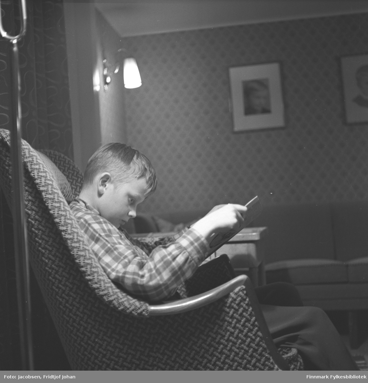 Arne Jacobsen sitter i en lenestol og leser en bok. Et bord står ved siden av lenestolen. Han har en rutet skjorte og ganske mørk bukse på seg. På veggen i bakgrunnen henger en lampe som er tent og et par bilder.