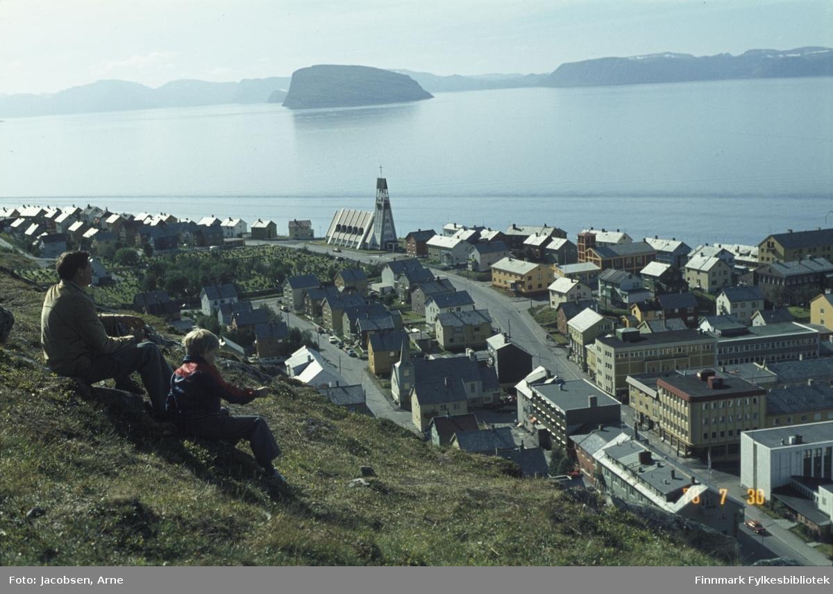 Deler av Hammerfest sentrum sett fra fjellet Salen. To personer sitter og ser utover byen en solfylt sommerdag. Veien som går gjennom sentrum er Rv 94, Strandgata som går over i Kirkegata ved rådhuskrysset nede til høyre i bildet. Der ligger også rådhuset. Kirka, midt på bildet, ligger på Haugen med kirkegården rett over veien. Øya Håja ses oppe i bildet og deler av Hjelmen kan skimtes bak den. Fjellene som går langs hele bildet i bakgrunnen er Sørøya.