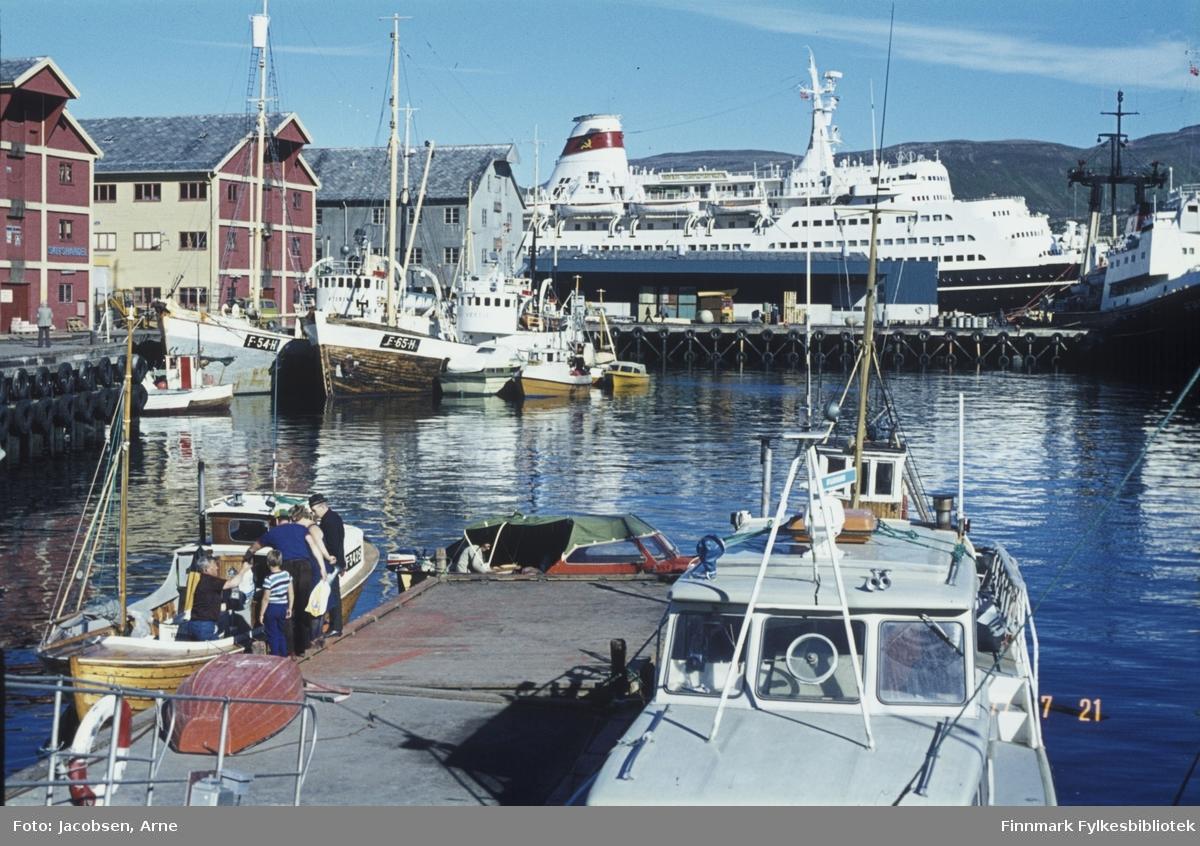 Hammerfest havn fotografert fra Jernteppet en flott sommerdag. Flytebrygga med landgangen ned fra kaia rett frem. Noen personer ses på flytebrygga og kaiene. Fem båter ligger der. En tresnekke til venstre og en cabincruiser til høyre. En jolle ligger hvelvet ved siden av snekka. En liten båt med påhengsmotor på kanten av brygga og en tresjark bak cabincruiseren. En del fiskefartøy og en hvalskute ligger fortøyd ved Nissenkaia. Et turistskip ligger ved dampskipskaia. En tråler ligger ved kai rett foran baugen på turistbåten. Byggene på kaia er, fra venstre: Nissen-gården, televerkbygget(nå biblioteket) og godsterminalen. Storfjellet ses over og foran turistskipet. Solskinn og blikkstille på sjøen.