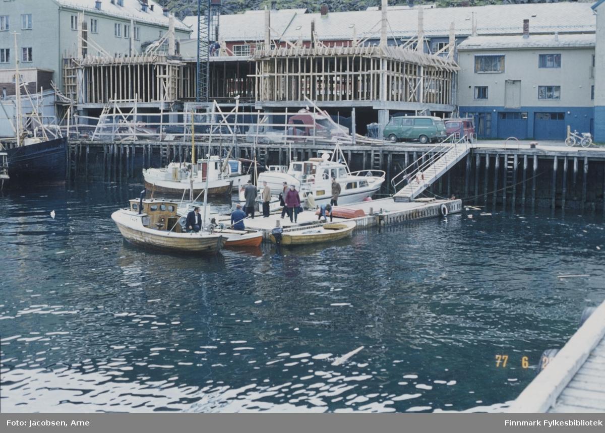 Jernteppet, indre havn i Hammerfest en fin sommerdag. Flytebrygga med landgang opp mot kaia der Domus-bygget er under oppføring. På enden av brygga ligger en snekke med en person på dekk. To åpne småbåter, en med påhengsmotor, og legeskyssbåten Streif Jr. ligger også ved brygga. Flere personer går på flytebrygga. På kaia står to varebiler og en tråsykkel. Ved kaia ligger en sjark fortøyd og baugen på en båt ses til venstre.