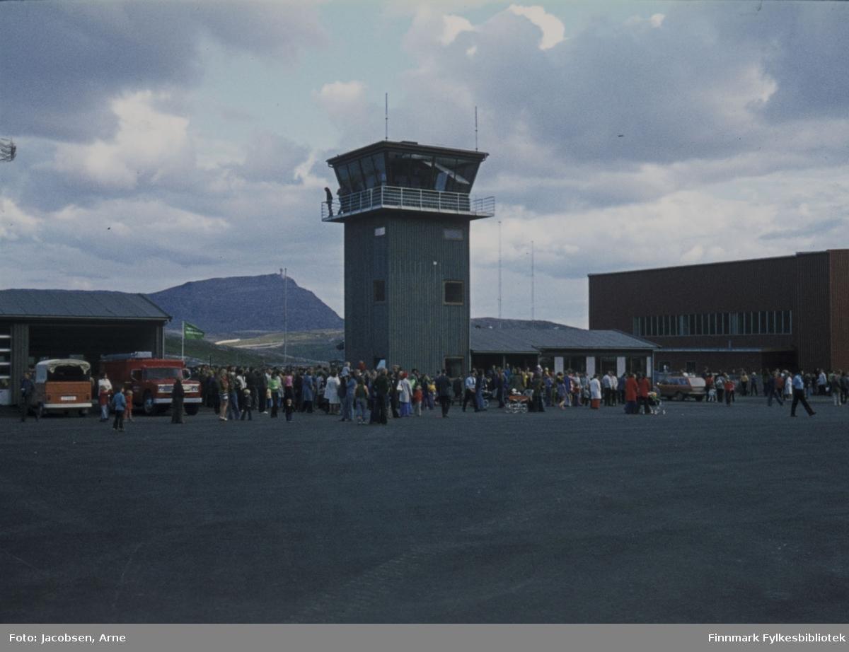 Fra åpningen av Hammerfest lufthavn 30. juli 1974. Flytårnet og passasjer-terminalen midt på bildet. Hangaren til høyre og il venstre står garasje, sannsynligvis for brann og redning. Mellom flytårnet og garasjen ses fjellet Tyven så bildet er tatt fra rullebanen. Byens befolkning møtte opp i hopetall til fest og flyshow. Overskyet, men oppholdsvær.
