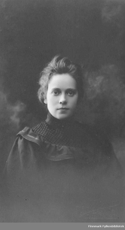 Portrett av ukjent kvinne. Hun er kledt i en mørk kjole eller bluse