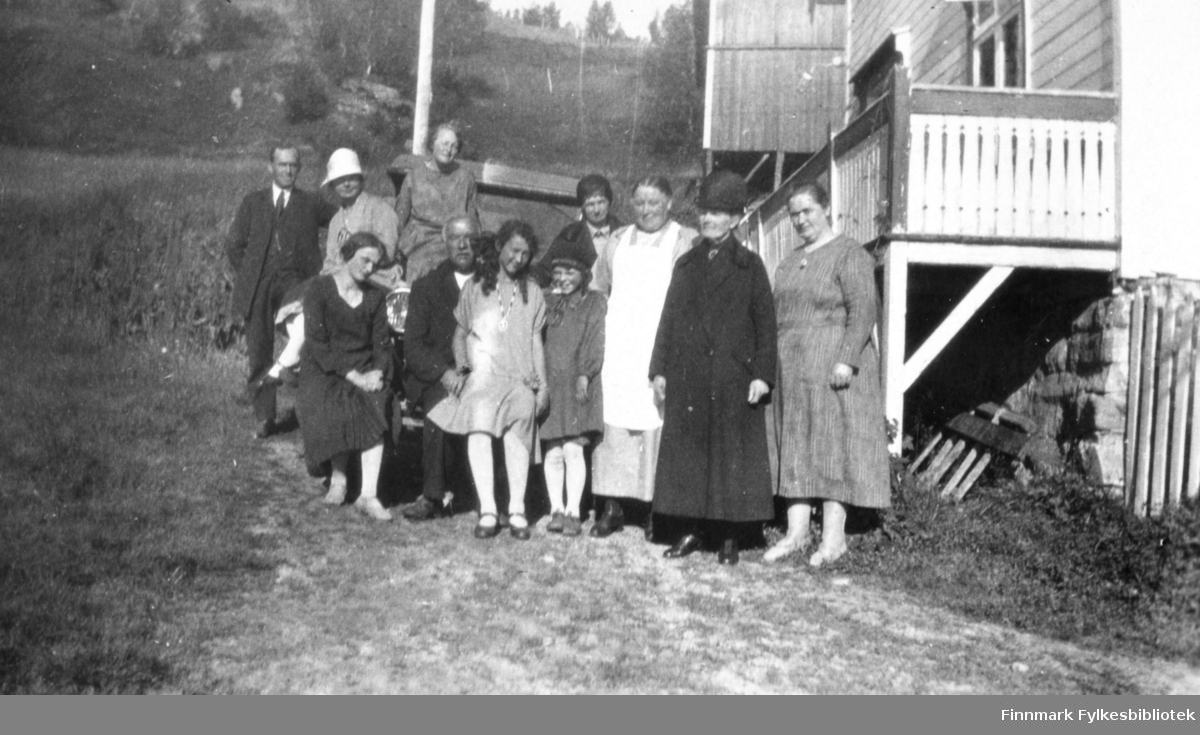 Fotografi av en gruppe personer som står uten for en veranda på et trehus. Huset er bygd oppå en mur. Det er muligens lærerinne Julie Jacobsen fra Vardø som står bakerst under stolpen. De andre, tre menn, fem kvinner og to jenter er ukjente. To av kvinnene har hatt på seg. Kvinnen som står som nummer tre fra høyre har på seg et hvitt forkle over kjolen. Kvinnen ved siden av henne har en lang mørk kåpe på seg. De andre kvinnene og jentene er kledt i kjoler. Mennene er kledt i mørke jakker og bukser. De har hvite skjorter. Mannen til venstre har slips