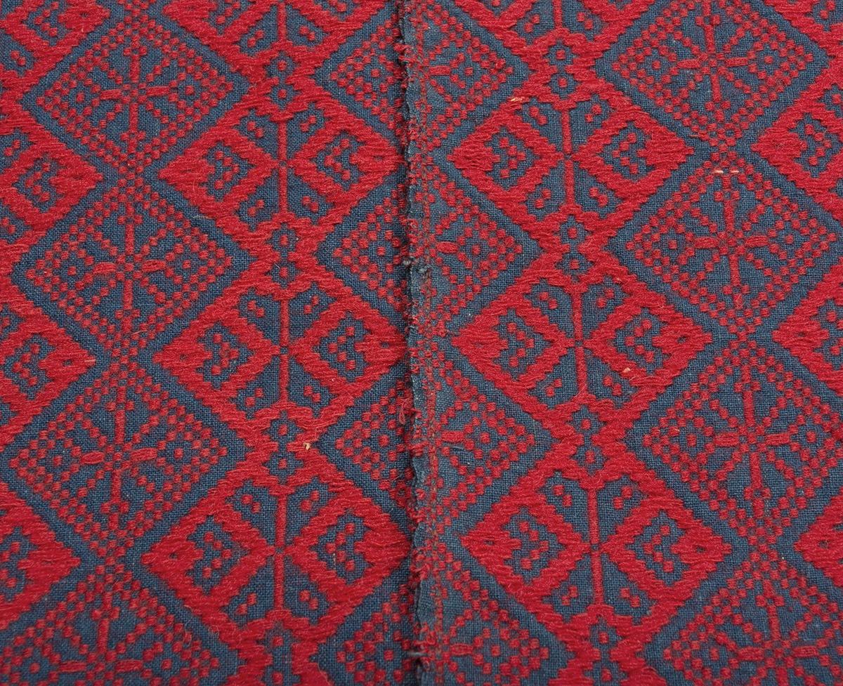 """Täcke vävt i opphämta. Skyttlat ytmönster av hjärtrosetter och stjärnor i lodräta ränder av snedställda rutor. Rött ullgarn i mönster på blå tuskaftsbotten i bomull. Täcket är ihopsytt på mitten av två delar. Fållad med smal fåll i kortsidorna. Stadkanter i långsidorna.Varp i indigoblått 2-trådigt s-tvinnat bomullsgarn, 18 trådar/cm.Botteninslag samma som varpgarnet, 18 inslag/cm.Mönsterinslag i 1-trådigt z-spunnet ullgarn, 16 inslag/cm.Täcket är märkt på baksidan med en påsydd tyglapp med texten: """"VÄVT AV ELNA OLSDOTTER F. 1828, S. WALLÖSA, SJÖRUP SN. TROL. VID HENNES GM. C:A 1850. GÅVA 1965 FRÅN: MARTIN OCH EMMA HANSSON LJUNITS HÄRAD"""". Intill sitter ett påsytt tygband med invävd text: """"SVENSK SLÖJD Malmöhus hemslöjd Malmö""""."""