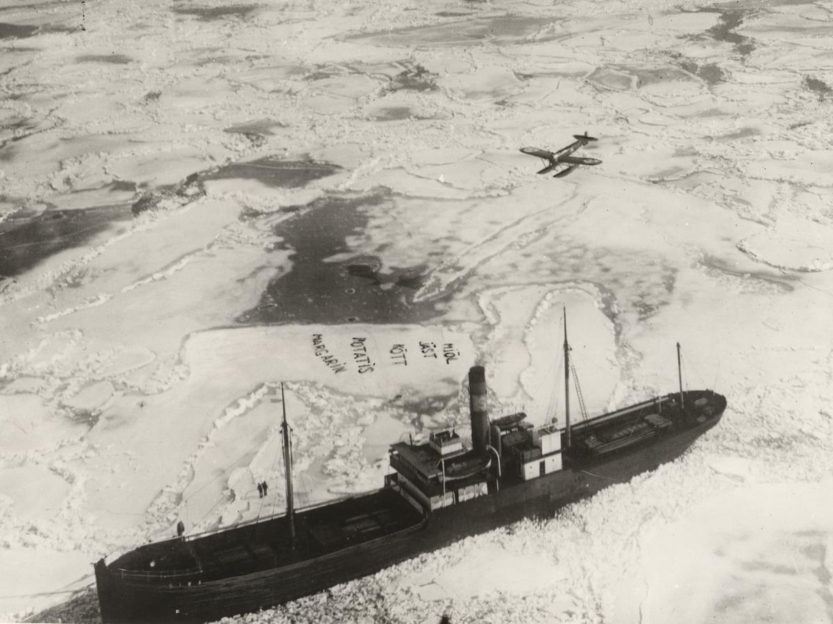 Ångfartyget SIVA fastskruvad i isen provianteras av flygplan. Foto taget den 23 februari 1929.