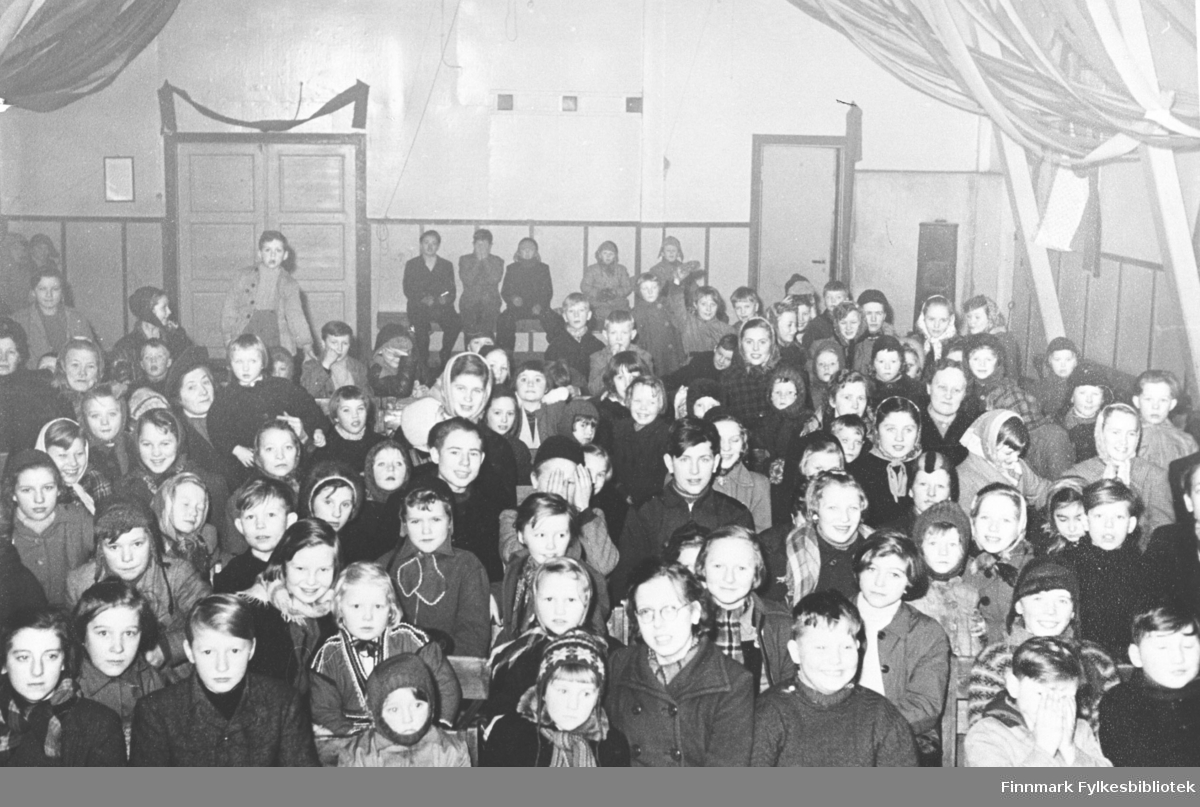 Bildet er tatt av pubikum som ser barneforestilling på Berlevåg samfunnsbrakke 1953.  Se egen navneliste.