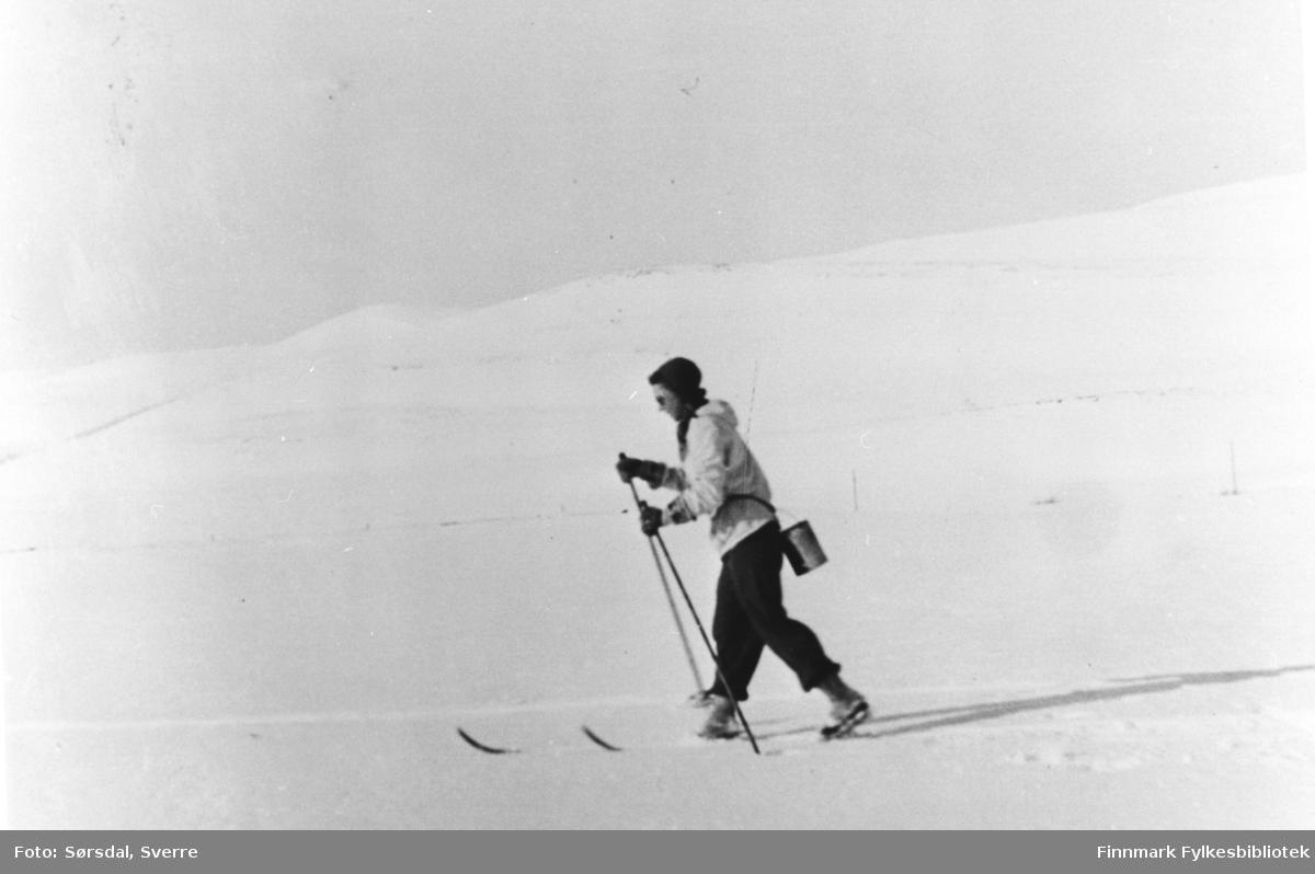 Else Sørsdal går på ski innover fra Hamna i Syltefjord for å hente melk hos gårdbrukere inne i fjorden. Årstallet er omtrent 1943-44. Melkespannet henger på ryggen.