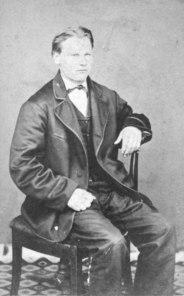 Et portrett av en ung mann, trolig av Johan Jonas. Han er kledd i jakke, vest, bukser, og har en søyfe rundt halsen. Han sitter på en stol. Bildet trolig tatt på slutten av 1800-tallet, begynnelsen av 1900-tallet.