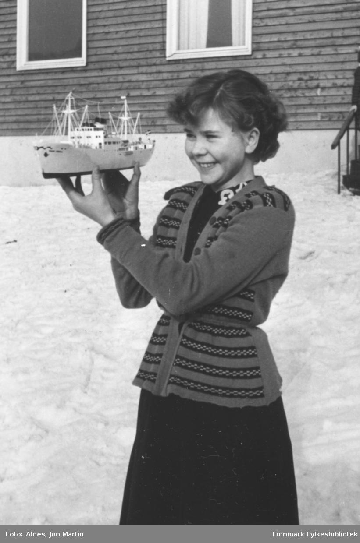 Randi Isaksen, elev i 6. klasse ved Øksfjord barneskole i 1954. Hun holder en modell av skolens kontaktskip 'Randi Brøvig'