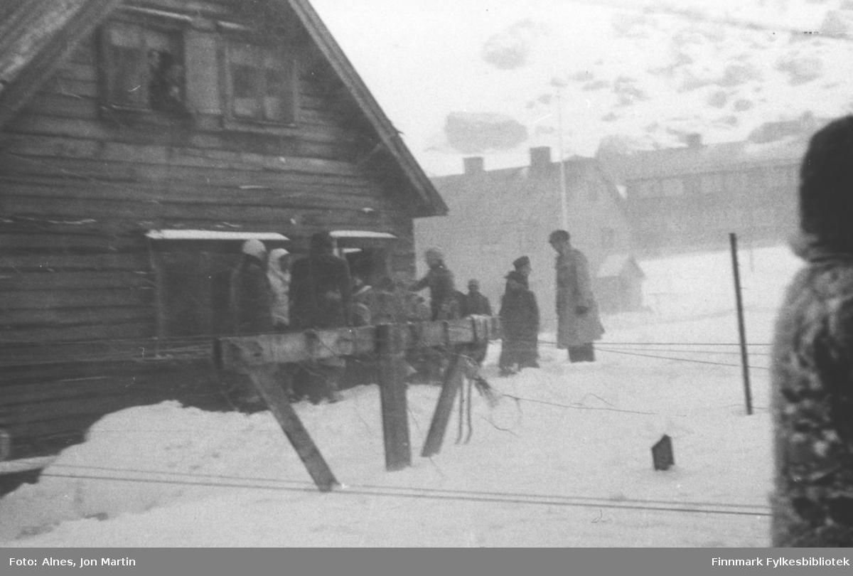 Skirenn i Øksfjord, 1954. Folk søker ly bak 'Hans Hansen-gården'. Helt bakerst i bildet prestegården