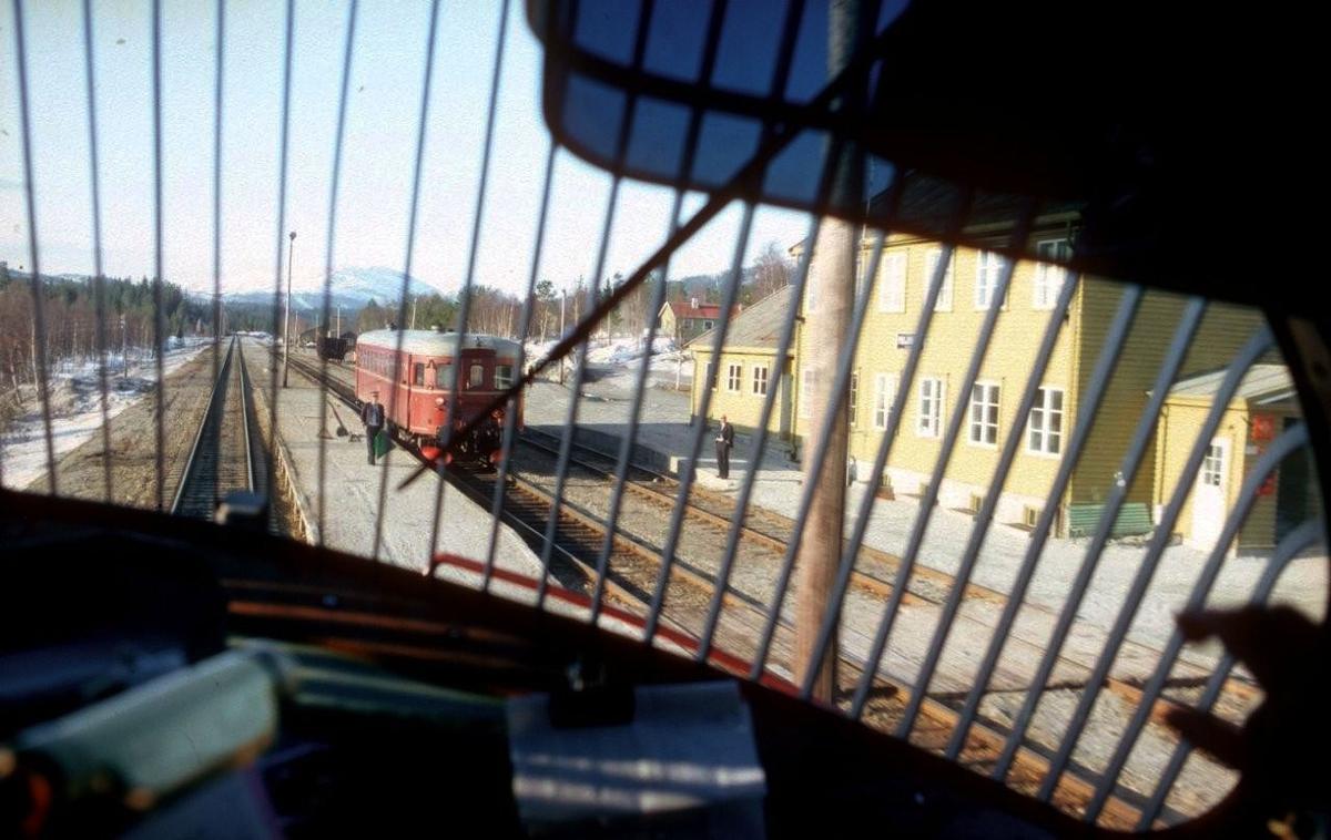 """Kryssing i Majavatn sett fra lokomotivet i godstog 5793 (Trondheim - Bodø) en lørdag. Lørdager byttet NSB motorvognen på Majavatn ved at det ble kjørt tomtog Majavatn - Grong - Majavatn. Togekspeditøren viser signal """"Passer"""" og lokomotivføreren i tomtoget står på plattformen til spor 1. Førerne som kjørte """"Majavassvogna"""" (Majavatn - Mo) var Trondheimsførere som lå på Majavatn en uke av gangen. Tjenesten var veldig attraktiv og krevde nærmere 40 års ansiennitet."""