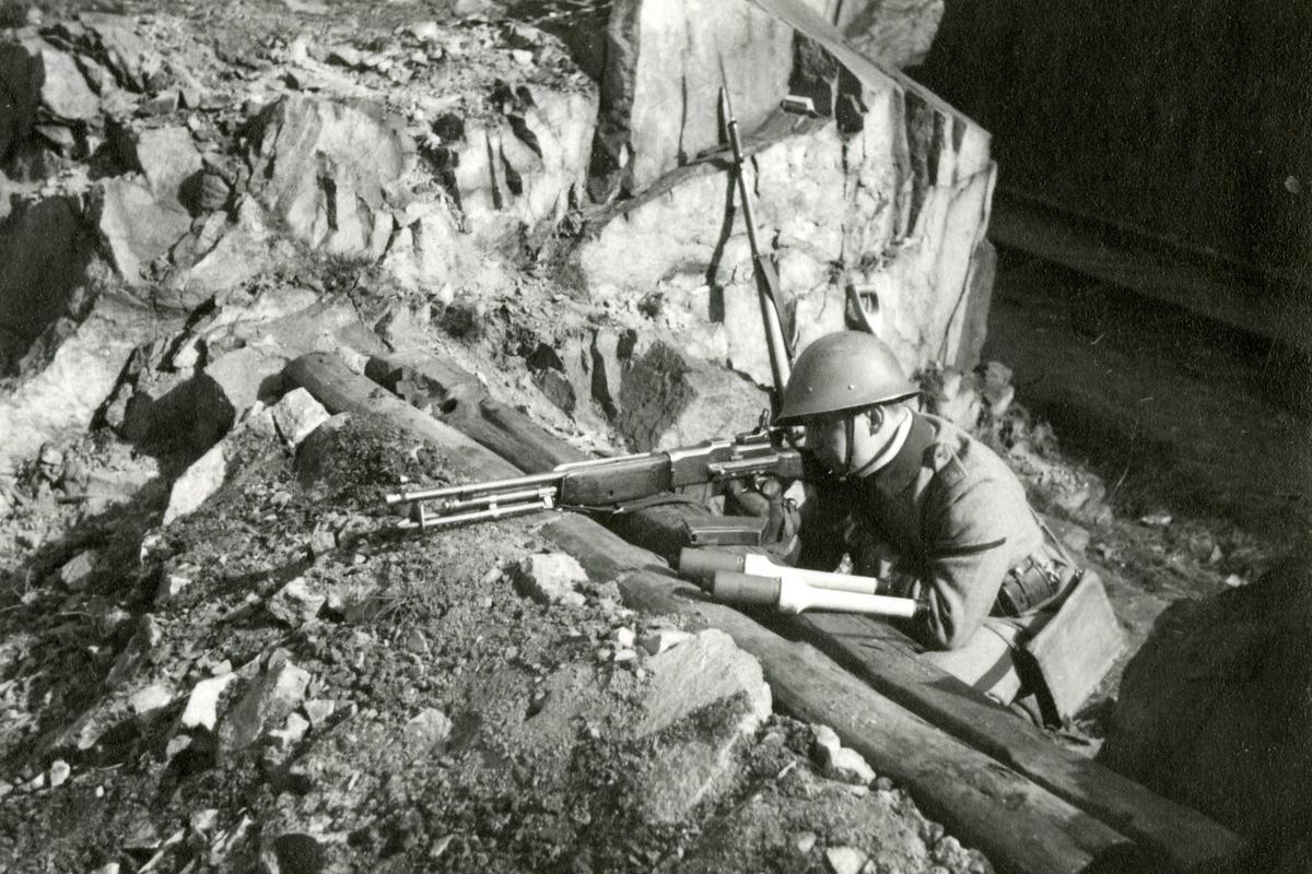 Soldat i skyttevärn med gevär och handgranater.