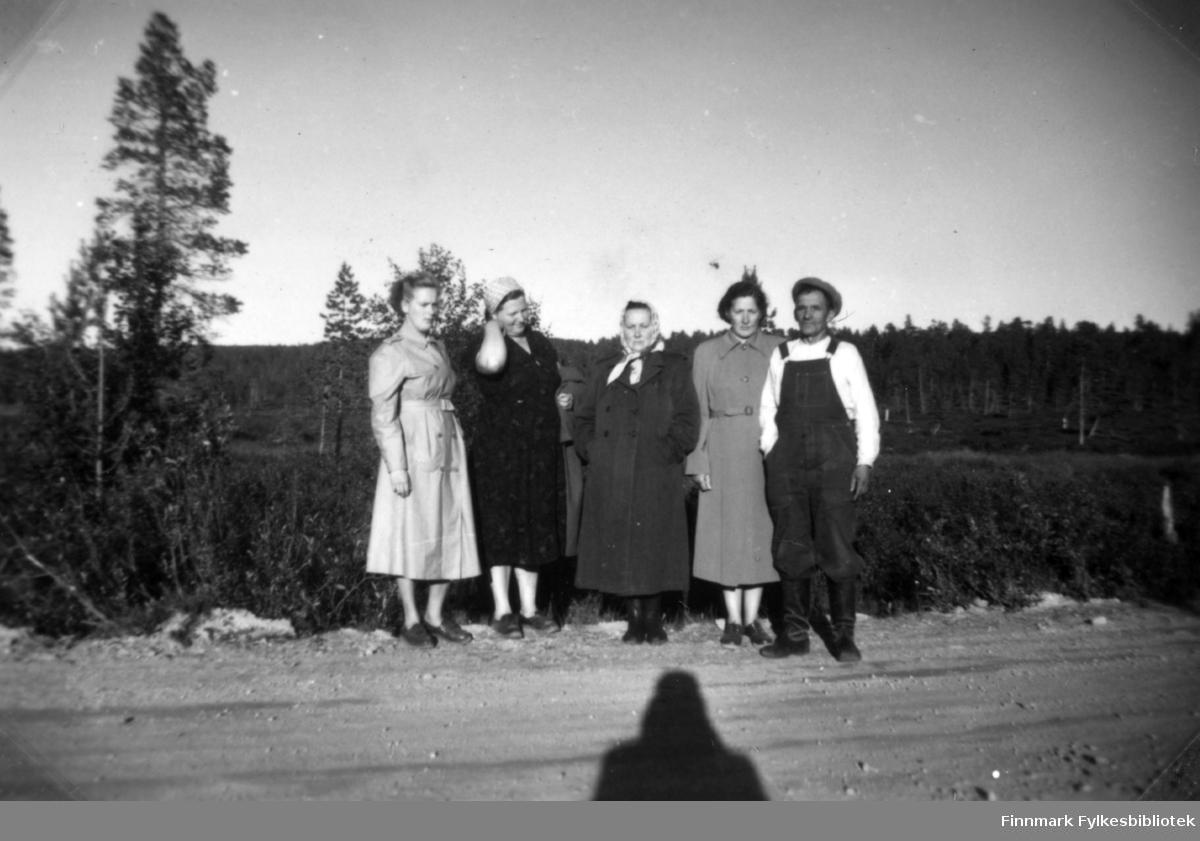 Fotografi av fire kvinner og en mann tatt på en grusvei. Fra venstre står Agnes Randa, Hilma Amanin, Maria Botti, Henrika Sotkajærvi og Alarik? Botti. Tre av kvinnene er kledt i kåper. Hilma bærer sin på armen. Hun har en mørk kjole på seg og et skaut på hodet. Alarik? er kledt i selebukse og lue. Det er skog i bakgrunnen