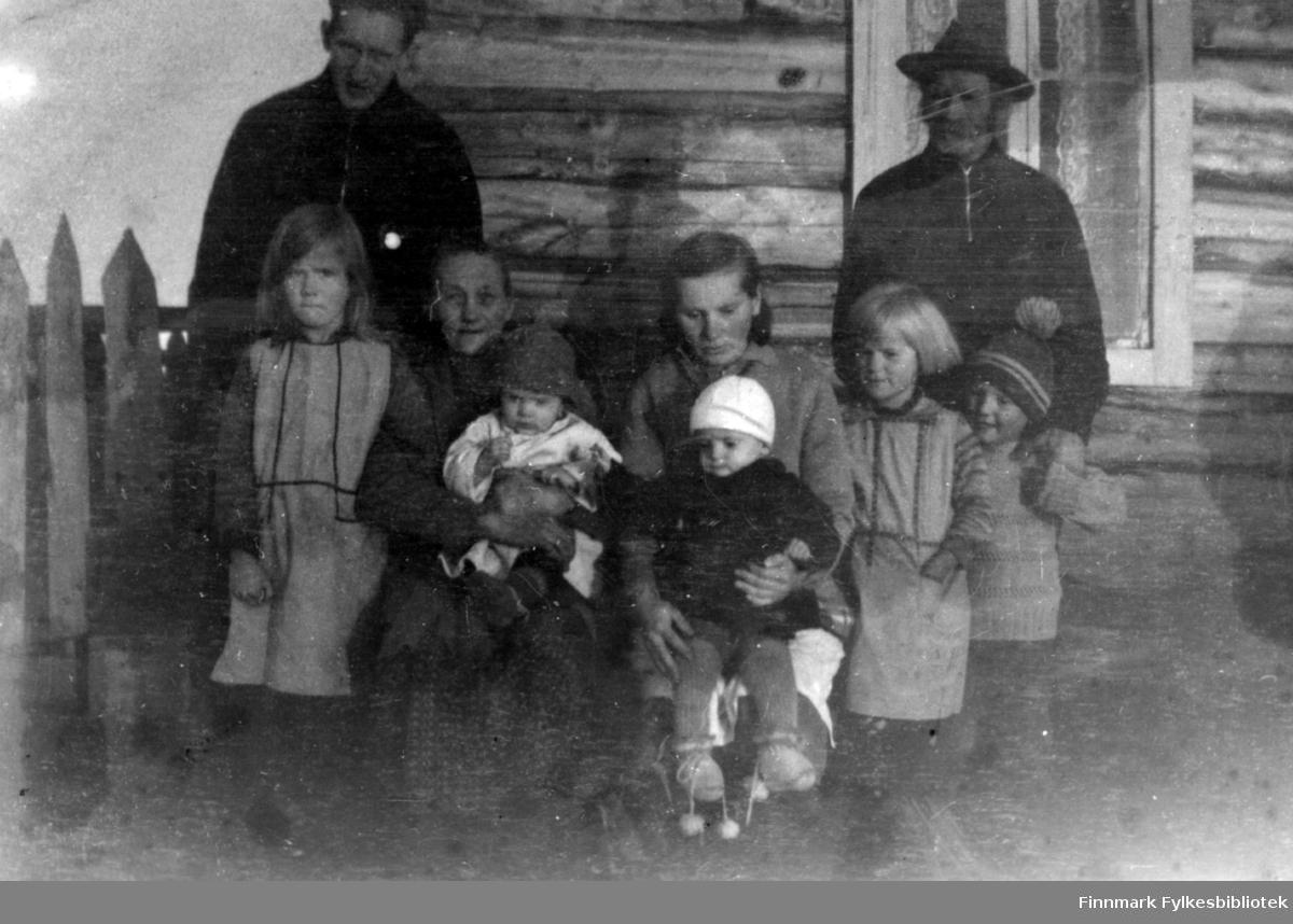 Fotografi av medlemmer av Stenbakk familien, på gården Stenbakk. Laila Julianne Berg (Stenbakk) står til venstre.  Helga Kristine Stenbakk (barnas mor) med Eila på fanget. Kaisa Sofie Stenbakk (Helgas mor)  med Egil på fanget . Johan Henrik Stenbakk (Aska) stående bak til høyre med Agnes og Bernhard foran seg (Kaisa sin mann). Egil og Eila er tvillinger. Mannen til venstre i bildet sies å være fotografen (selvutløser?) navn ukjent. Bildet må være tatt i ca. 1933-34.