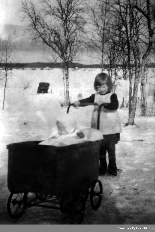 Fotografi av Mirjam Kälkäjä (f. Ranta) som står og holder i en barnevogn. I vogna sitter hennes lillebror Jarkko. Bildet er antatt å være fra ca. 1944 og er tatt på finsk side av Pasvik.