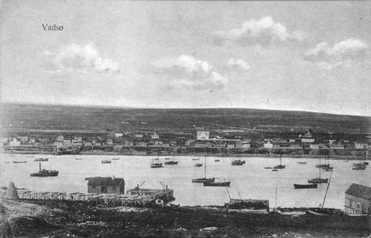 Vadsø fotografert fra Vadsøya, bildet gir god oversikt over bebyggelsen i vestre del av byen. Den store lyse bygningen sentralt i bildet er Esbensens hus på Bakken. I forgrunnen kaier og pakkhus på øya, samt en del båter på havna. Fotografisk postkort