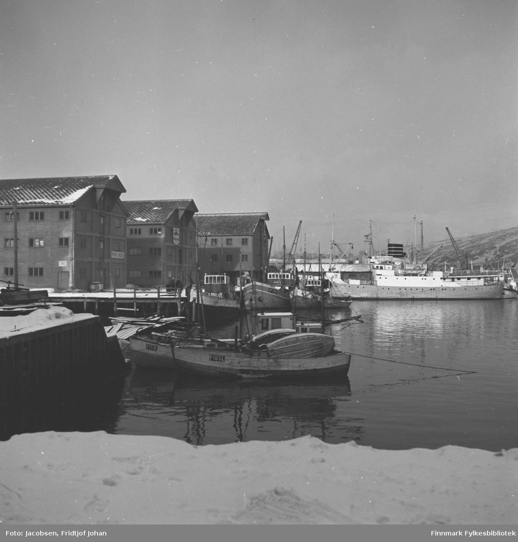Hammerfest havn med noen fiskebåter ved kai. Den store båten til høyre i bildet er en FFR-båt, MS Brynilen (den har navnet etter et sted i Loppa kommune, nær grensa til Kvænangen). Bak Brynilen ligger den bergenske 15-mileren MS Ara. De store byggene på kaia er Trygve Nissens forretning og lager. Lengst borte ligger Televerkets lager som i dag huser biblioteket.