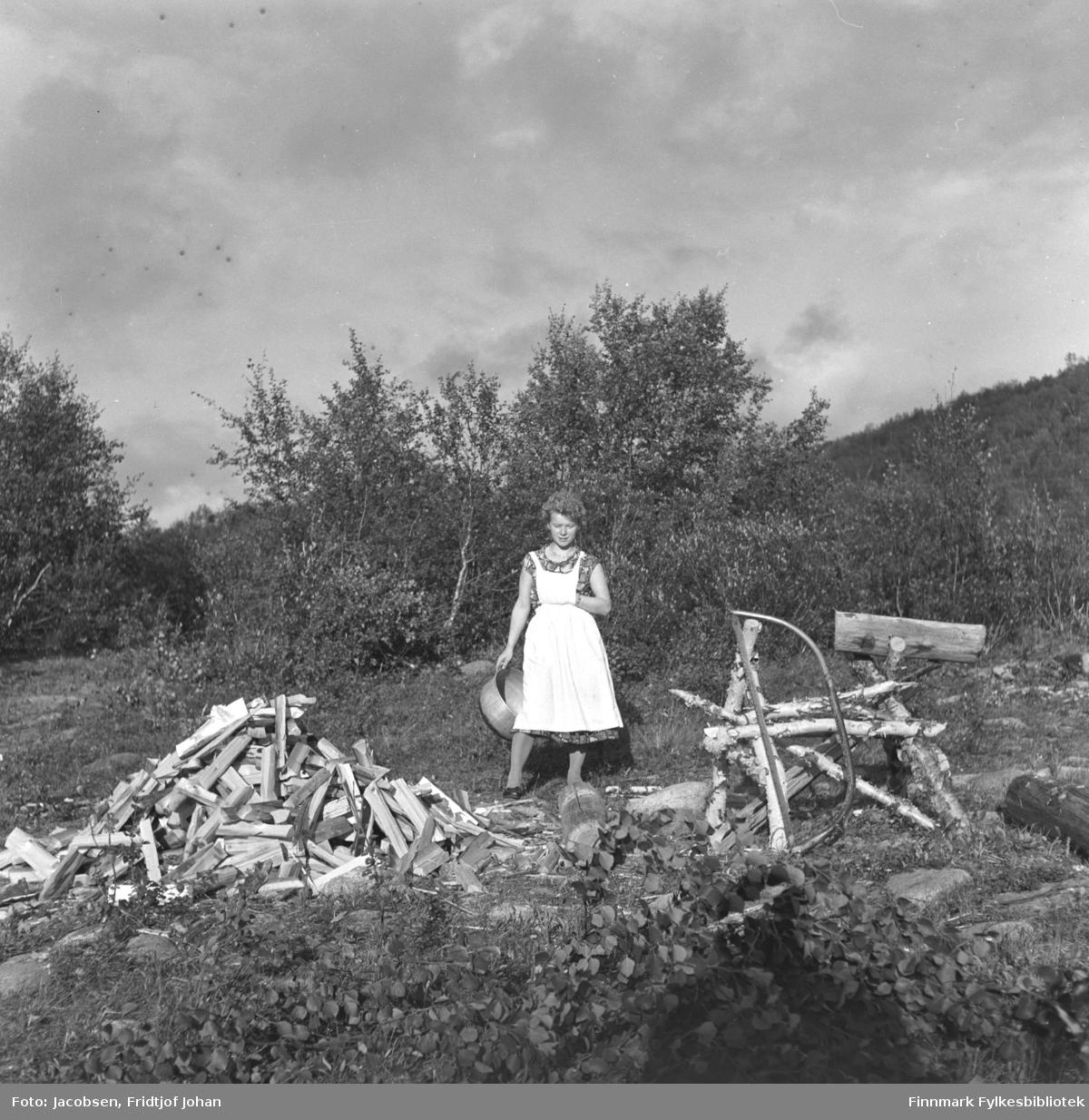 En kvinne står rett bak en hjemmelaget sagstol og en haug med ved.
