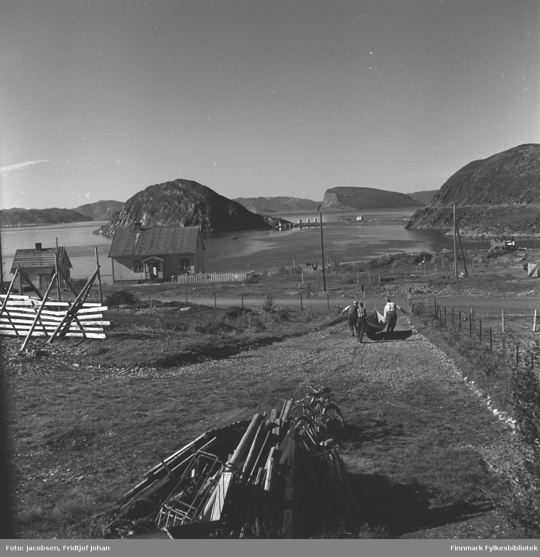 Arne Nakken, Øystein Nakken og Fridtjof Jacobsen bærer Arne Nakkens selvbygde Nordlandsbåt mot sjøen i Rypefjord. Mellom fjellene Rypklubben og Rypefjell ses øya Håja.