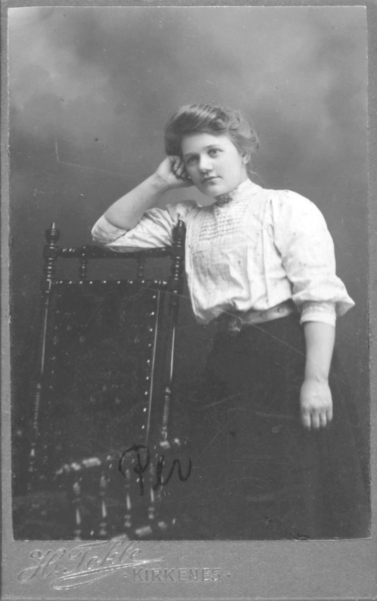 Portrett av en ung kvinne, Andrea Persen. Hun står ved en vakker ornamentert stol og lener seg mot ryggstøet med den høyre armen.  Hun er kledd i en lys bluse og et mørkt, langt skjørt. I livet har hun et belte med en stor beltespenne. Andrea Persen var født i Vadsø i 1887.  Bildet er tatt i Kirkenes hos fotograf Helga Tokle. Helga Elise Tokle var født i 1871 i Sør-Varanger og døde i 1975. Hun virket i Kirkenes i perioden 1900-1922, da hun overtok Gustav Lindmans Atelier i Drøbak og flyttet fra Finnmark. Tokle var datter avlærer og kirkesanger Anders Tokle og Kristoffa.