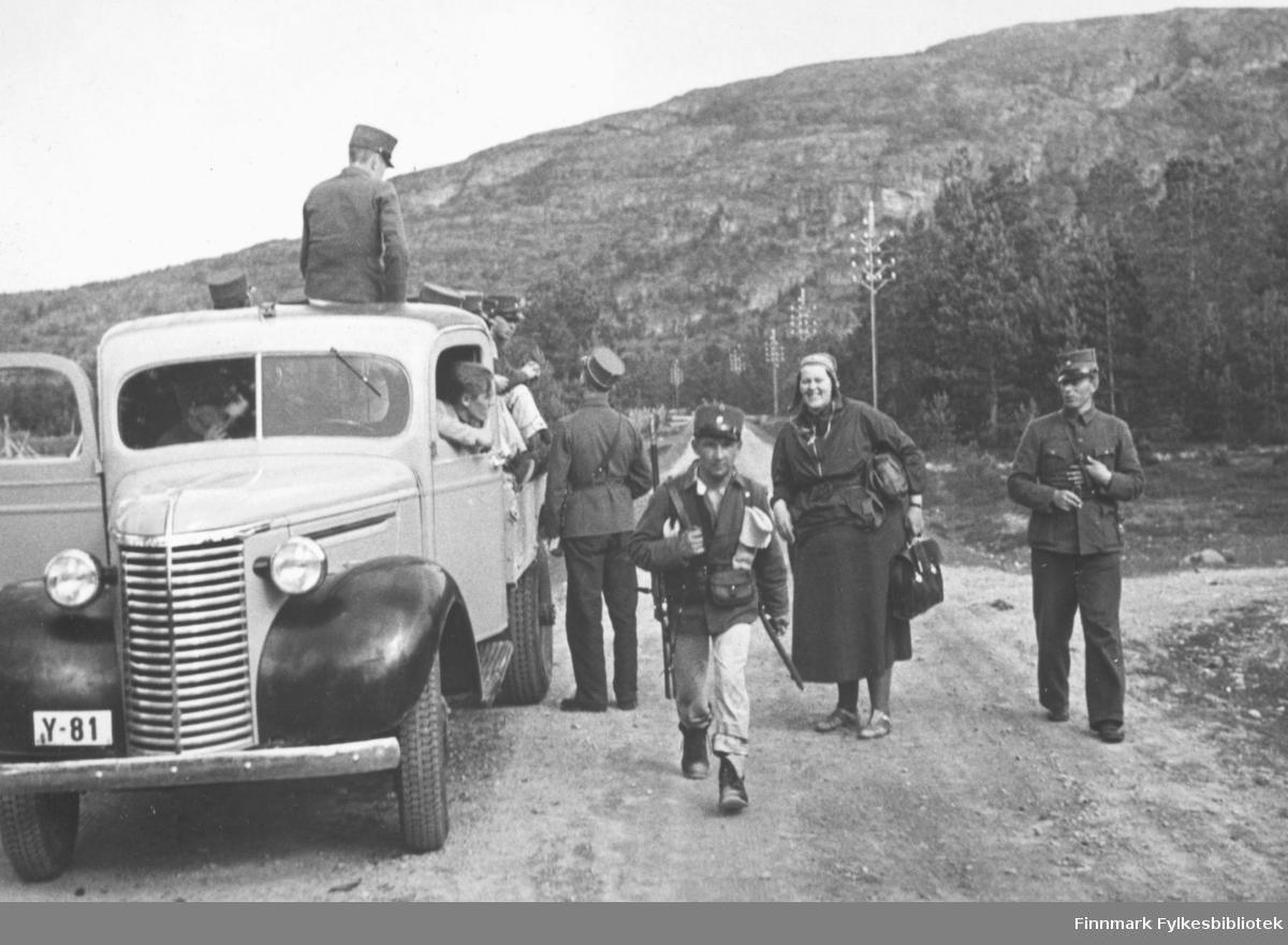 """Soldater laster proviant opp på planet til lastebil Y-81. Innskrift i album: """"Vi kjører fra matstasjonen"""". Chevrolet 1939 med norskbygd førerhus."""