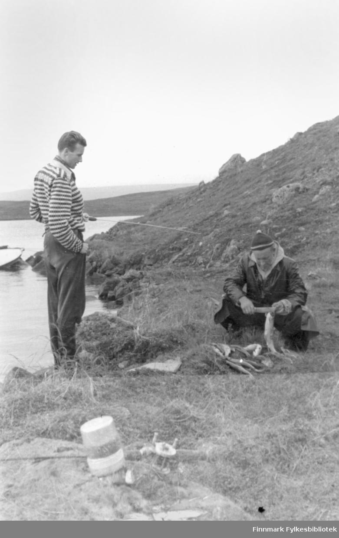 Bildet er tatt fra en fisketur til Peskvannet august 1955. Turkameratene hadde tatt seg dit med sjøfly og hadde med telt for å fiske ved vannet. Ernst Lebesby stod for mye av sløyingen ved Peskvannet, de andre ville heller fiske.  Foto: Ole Gustav Øverdahl.