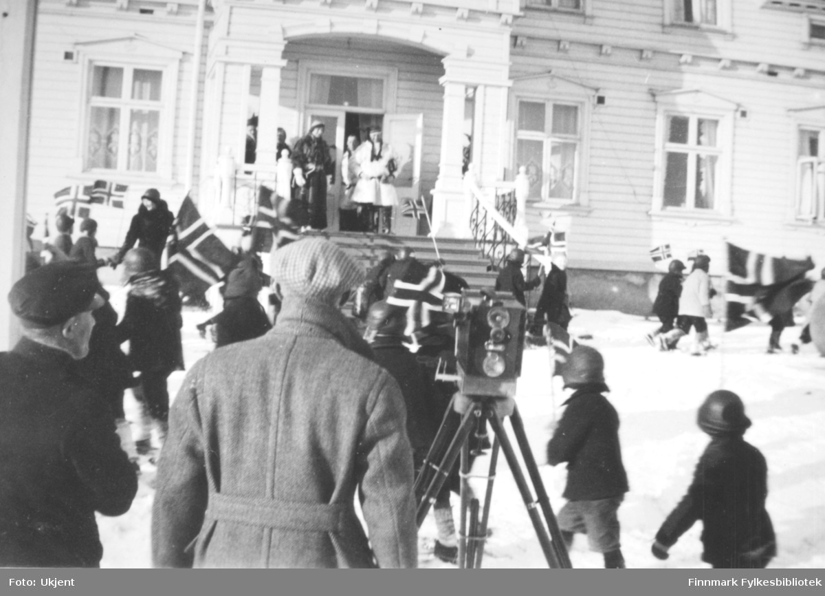 Ved avslutningen av kronprinsparets påsketur over Finnmarksvidda i 1934 defilerte skolebarna og speiderne foran hovedtrappa på Fylkesgården i Vadsø. Kronprinsparet stod iført det utstyret de hadde brukt på turen- pesk og skaller- sammen med adjutanten, oberst Østgaard og frue, og fylkesmann Hans Gabrielsen og hans kone, Sara Gabrielsen. Midt i bildet sees et trekamera på stativ. Barna og speiderne vifter med norske flagg.