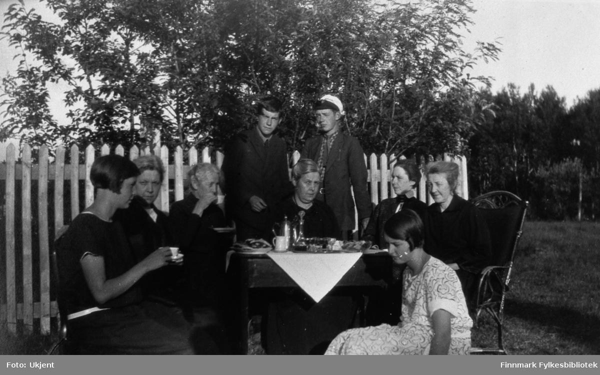 Her sitter en gruppe av mennesker i hagen på lensmannsgården Kveldro i Jarfjord. Stående helt bakerst er Kaare Espolin Johnson og Einar Bertelsen. Den unge damen som sitter helt ytterst til venstre med en kopp i hånden er Elsa Bertelsen. De to eldre damene til venstre for henne er Gunda og Thora Bertelsen (sansyndligvis i den rekkefølgen, litt usikkert). Til venstre for dem igjen (sittende foran guttene) er Bergljot Johnson (f.Bertelsen). Til venstre for henne sitter fru Aagot Bertelsen, Aasta Bertelsen og til slutt den unge piken Aagot Bertelsen. Damene har på seg kjoler. Guttene har på seg jakker, skjorter og slips. Einar har på seg en hatt. På bordet kan man se en duk, te/kaffekanne, kopper, fat, bestikk og tydeligvis noe mat. Man kan se at Aasta Bertelsen til høyre sitter på en dekorativ stol. Gruppen sitten foran er gjerdet og man kan se trær i bakgrunnen.