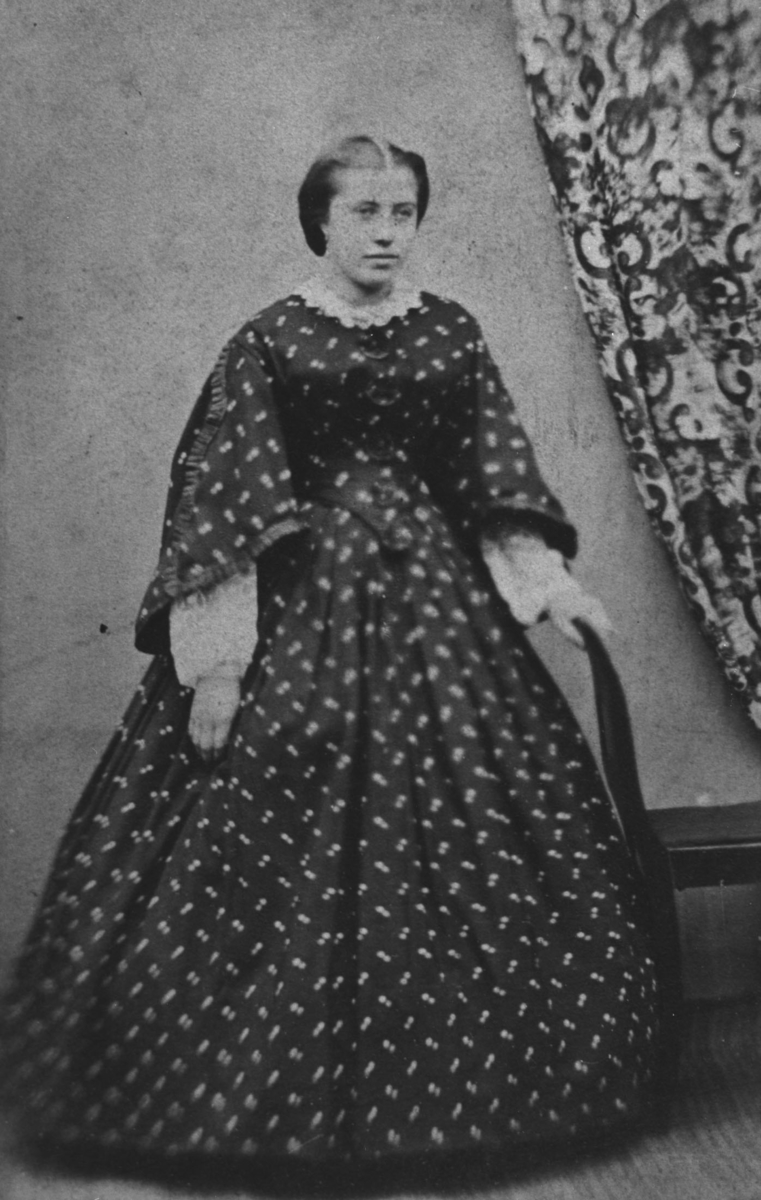 Portrett av en ung kvinne, kvinnen er ukjent. Bildet er gammel, ca fra 1860, kan også være litt eldre. Den unge damen står ved veggen, det henger en mønstrert gardin på veggen. Handen hennes ligger på ryggstøen av en stol. Hun er kledd i en mørk kjole med brede ermer, stram midje og veldig bredt fald. Typisk for 1860 årene/og tidligere