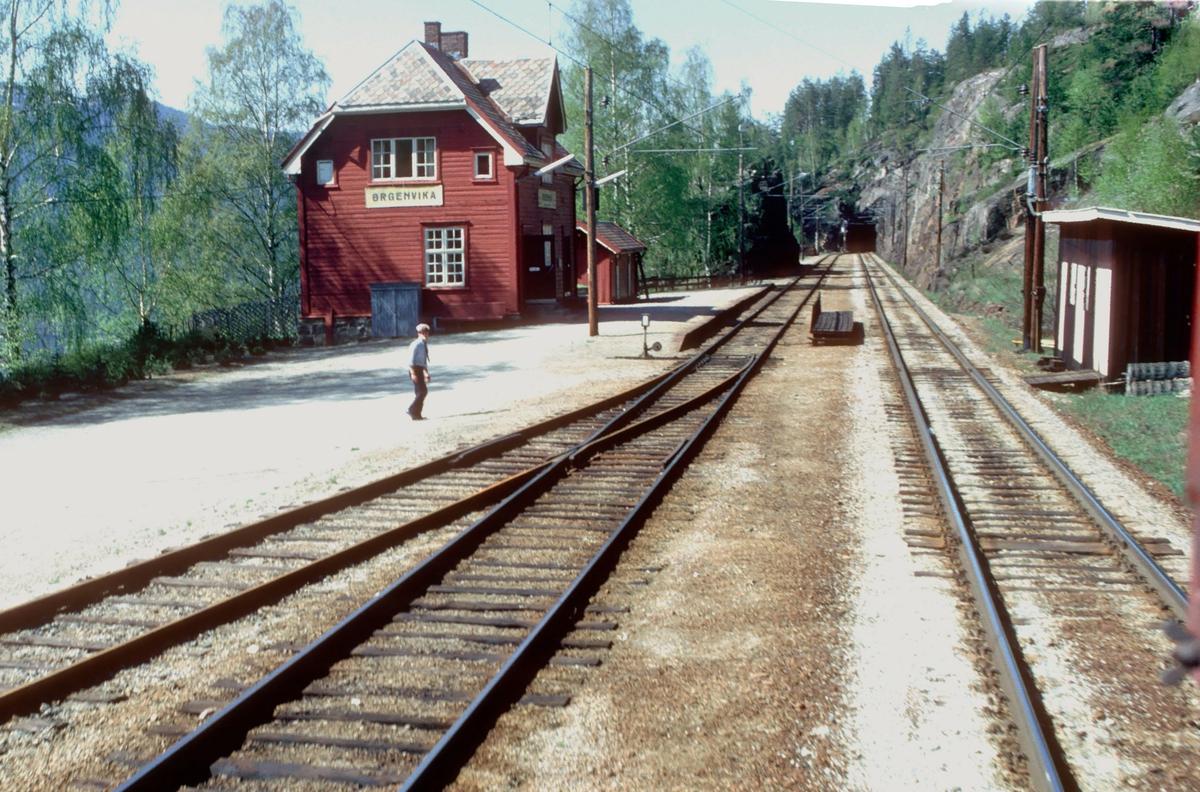 Utsikt fra lokomotivet i godstog 5501 under passering av Ørgenvika stasjon. Utkjørhovedsignalet viser kjørsignal, og vi ser togekspeditøren.