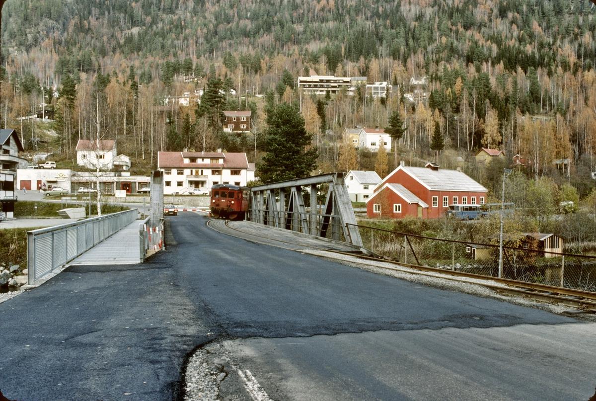 Persontog til Kongsberg under utkjøring fra Rødberg stasjon. Toget kjørte her over felles bro med vei.