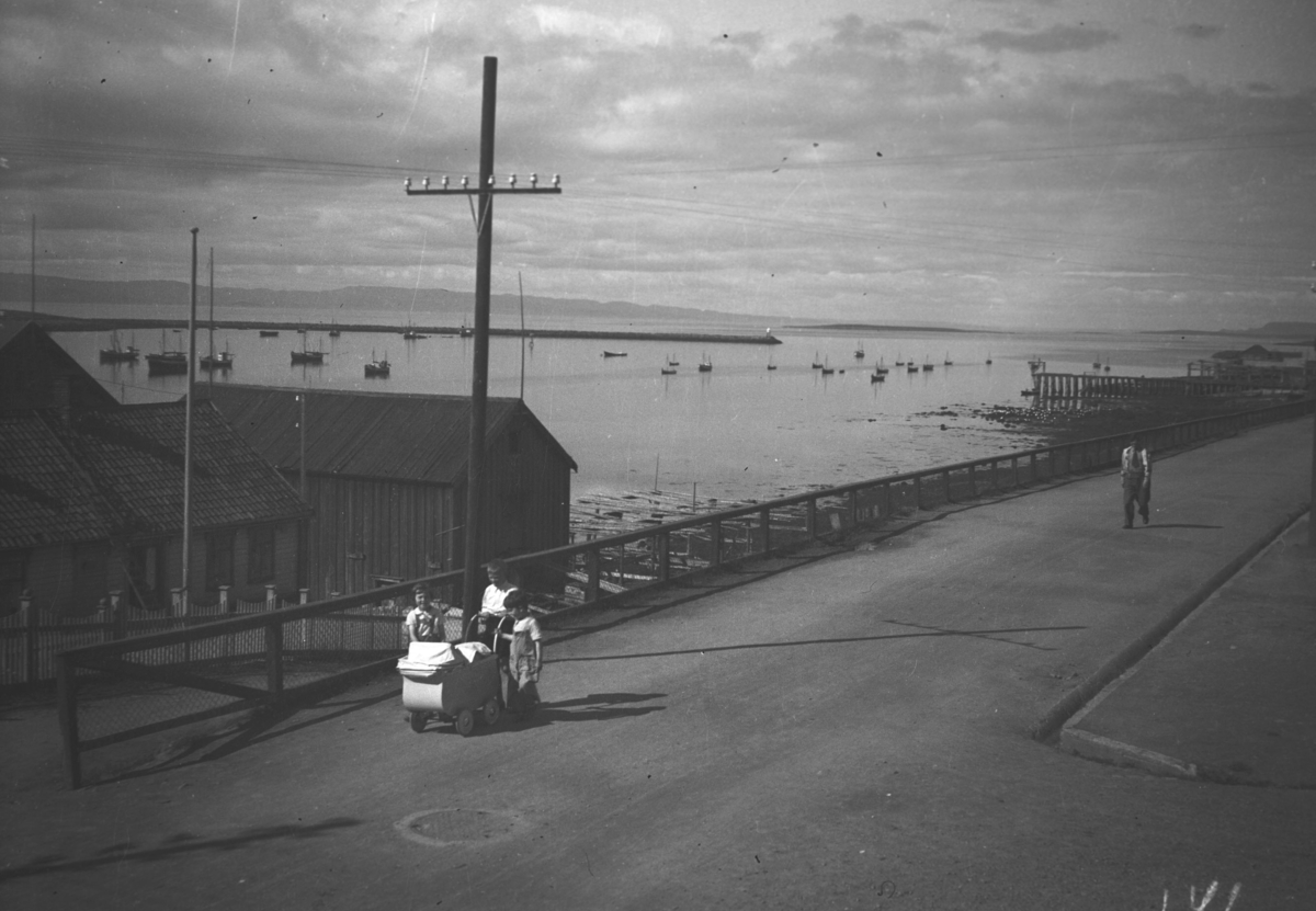 En barnevogn trilles oppover Havnegata, barna bak den er ukjente. Nordahls fiskefabrikk ses til venstre på bildet og Bekola-kaia til høyre. Mange småbåter ligger fortøyd ute i havna.