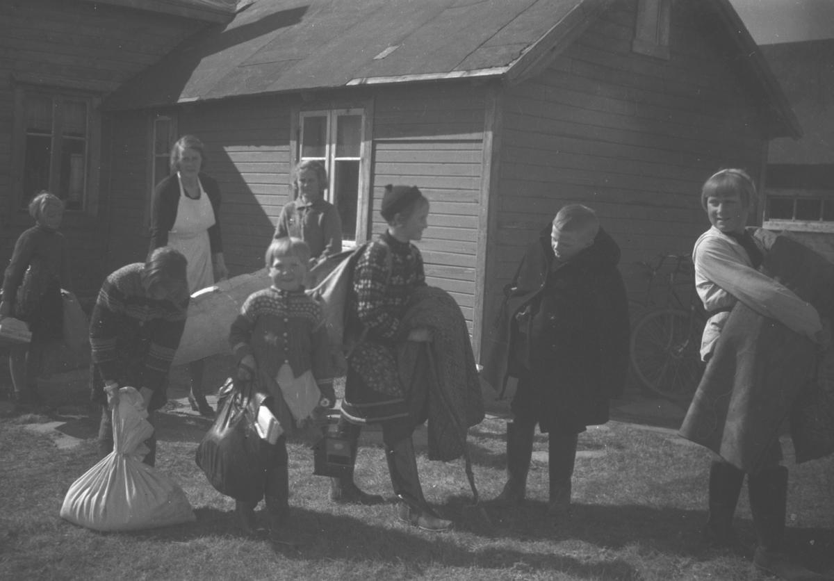 Flytting i Andersby. Flere mennesker utenfor et hus med sekker og andre ting i hendene. Tor Hauge står som nr. 2 fra høyre på bildet.