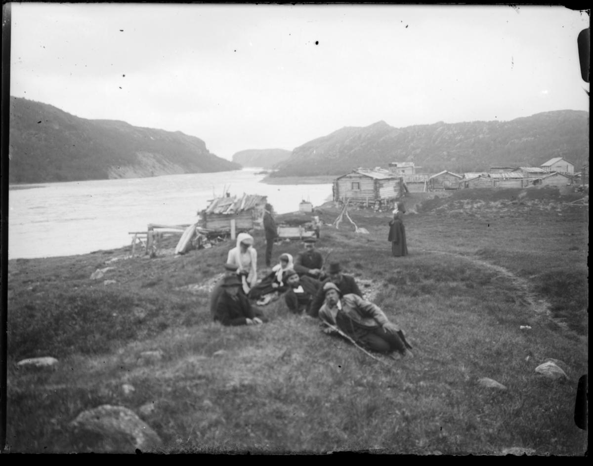 Boris Gleb. Seks menn og to kvinner hviler i gresset ved skoltebyen. En mann og en kvinne står litt bakenfor. Husene i skoltebyen er bygd av laftet tømmer. Pasvikelva renner forbi
