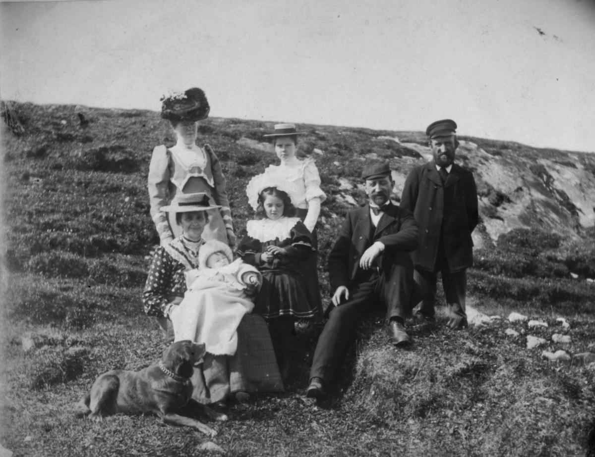 8.juli 1906. Perlemors føreste skogtur. En dame sitter på bakken med en baby på fanget. Ved siden av seg en hund.En liten pike står bak henn. Hun har en mørk kjole med stor hvit brodert krage på. På hodet en hvit hatt. Bak henne en ung jente i hvit blondebluse og hatt på hodet. Karoline Ohlsen står ved siden av. Til høyre for de sitter en mann på en knau og en mann står bak han.
