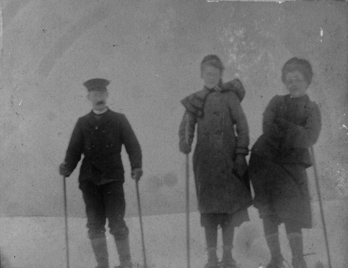 To damer og en herre på ski.