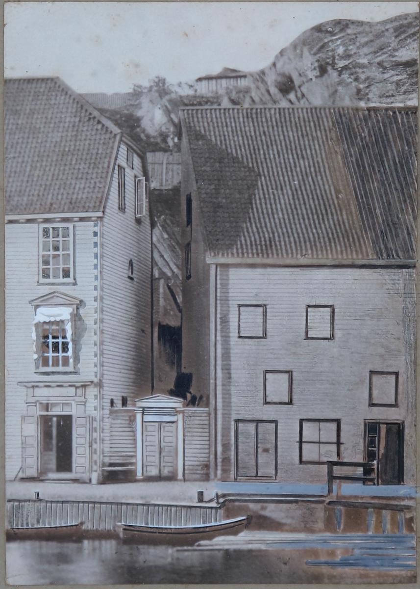 To bygninger med dør/vegg imellom. I forgrunnen brygge og robåter. Rankeaktig dekor på ramma.   Et våningshus med halvvalmet tak, og en sjøbod, begge i tre etasjer. Dør i våningshuset omrammet av klassisistisk portal. Smårutet vindu uten midtpost, 3 x 4 ruter.